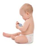 Det lyckliga barnet behandla som ett barn litet barnsammanträde som ler och spelar med mobilen Royaltyfria Foton