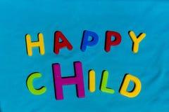 Det lyckliga barnet för ord som är skriftligt vid leksakbokstäver Arkivfoto