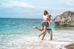 Det lyckliga barnet firar smekmånad par som har gyckel på stranden Hav tropisk semester på den Bali ön, Indonesien royaltyfri bild