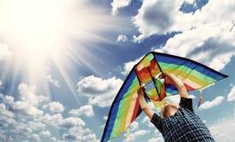 Det lyckliga barnet flyger en drake i skyen 2 Royaltyfri Fotografi