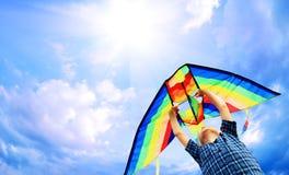 Det lyckliga barnet flyger en drake i skyen Fotografering för Bildbyråer
