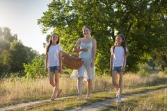 Det lyckliga barnet fostrar att gå med två döttrar i fält på solnedgången arkivfoton