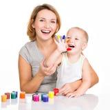 Det lyckliga barnet fostrar och barnet med målade händer Royaltyfri Foto