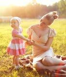 Det lyckliga barnet fostrar och behandla som ett barn den lilla dottern som bär en klänning Fotografering för Bildbyråer