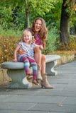 Det lyckliga barnet fostrar och behandla som ett barn den talande mobiltelefonen för flickan i stad parkerar Arkivfoto