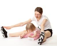 Det lyckliga barnet fostrar, och hennes lilla dotter som gör sporten, övar arkivfoton