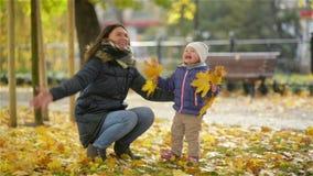Det lyckliga barnet fostrar och hennes lilla dotter som har gyckel i en Autumn Park, en mamma och en flicka som kastar sidor och  arkivfilmer