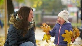 Det lyckliga barnet fostrar och hennes lilla dotter som har gyckel i en Autumn Park, en mamma och en flicka som kastar sidor och  stock video