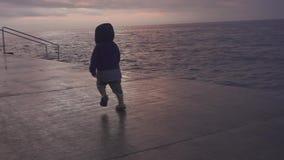 Det lyckliga barnet har gyckel i havsstranden Ungelek på havet Pojkespring på havskusten semester med ungen roligt vatten arkivfilmer