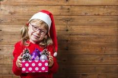 Det lyckliga barnet i den santa hatten som rymmer en ask med jul, klumpa ihop sig på a Royaltyfri Fotografi