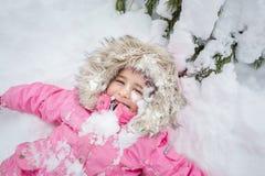 Det lyckliga barnet i vinterskog behandla som ett barn flickan i ett rosa omslag som ligger i snön arkivfoto