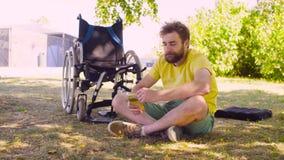 Det lyckliga barnet inaktiverar mansammanträde på gräset i parkera stock video