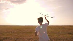 Det lyckliga barnet kör med ett leksakflygplan på en solnedgångbakgrund över ett fält Begreppet av en lycklig familj Barndom arkivfilmer