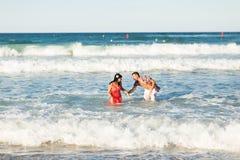 Det lyckliga barnet kopplar ihop att ha gyckel, mannen och kvinnan i havet på en strand Royaltyfria Foton