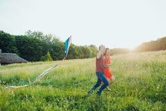 Det lyckliga barnet kopplar ihop förälskad spring en drake på fältet Två, man och kvinna som ler och vilar i landssidan Arkivbilder