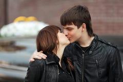 Det lyckliga barnet kopplar ihop förälskat kyssa som är utomhus- Arkivbild