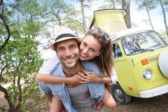 Det lyckliga barnet kopplar ihop framme av den campa skåpbilen fotografering för bildbyråer