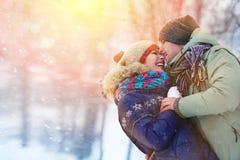 Det lyckliga barnet kopplar ihop i vinter parkerar att skratta och att ha gyckel familj utomhus fotografering för bildbyråer