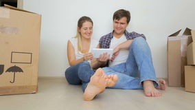 Det lyckliga barnet kopplar ihop köpande nytt möblemang till deras lägenhet efter renovering stock video