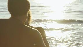 Det lyckliga barnet kopplar ihop lek i bränningvågor på den sandiga stranden Den stiliga mannen virvlar runt rymma händer med den lager videofilmer