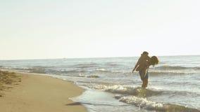 Det lyckliga barnet kopplar ihop lek nära kusten i bränningvågor på den sandiga stranden Den stiliga mannen rymmer den nätta flic stock video
