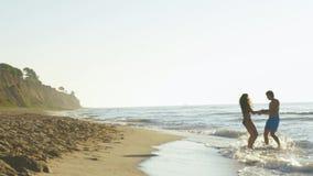 Det lyckliga barnet kopplar ihop lek nära kusten i bränningvågor på den sandiga stranden Stiliga manswirs med den nätta flickan l stock video