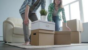 Det lyckliga barnet kopplar ihop med kartongflyttningar till den nya lägenheten stock video