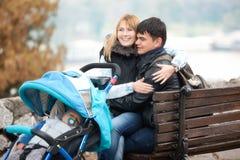 Det lyckliga barnet kopplar ihop sammanträde med lite sonen i barnvagn fotografering för bildbyråer
