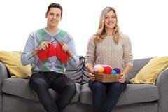 Det lyckliga barnet kopplar ihop sammanträde på en soffa och ett handarbete tillsammans royaltyfri foto