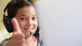 Det lyckliga barnet lyssnar musik och spela på datoren med utomhus- hörlurar lager videofilmer