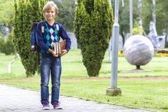 Det lyckliga barnet med en ryggsäck och böcker går till skolan utomhus- Royaltyfri Bild