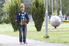 Det lyckliga barnet med en ryggsäck och böcker går till skolan utomhus- Royaltyfri Fotografi