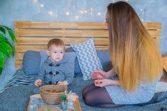 Det lyckliga barnet moder och henne behandla som ett barn sonen som spelar med valnötter royaltyfri bild