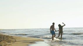 Det lyckliga barnet parar lek nära kusten i bränningvågor på den sandiga stranden långsam rörelse arkivfilmer