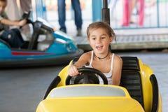 Det lyckliga barnet rider elbilen på parkera Arkivbild