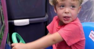 Det lyckliga barnet rotera styrninghjulet stock video