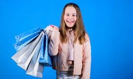 Det lyckliga barnet shoppar in med p?sar Shoppa daglycka k?p kl?der Hemfallen k?pare f?r Fashionista Modeboutiqueungar royaltyfri fotografi