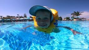 Det lyckliga barnet simmar i en flytväst arkivfilmer
