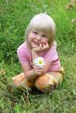 Det lyckliga barnet sitter på äng med blomman räcker in. Royaltyfria Foton