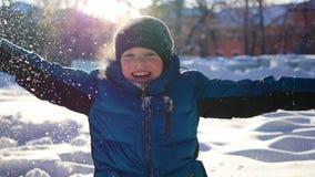 Det lyckliga barnet som har gyckel i vinter, parkerar på en solig dag Royaltyfri Fotografi