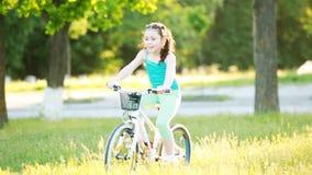 Det lyckliga barnet som rider en cykel i staden, parkerar på den varma dagen för sommar stock video