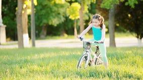 Det lyckliga barnet som rider en cykel i staden, parkerar på den varma dagen för sommar lager videofilmer