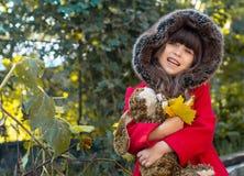 Det lyckliga barnet som spelar i höst, parkerar Lövverk för nedgång för ungesammankomstguling royaltyfri fotografi