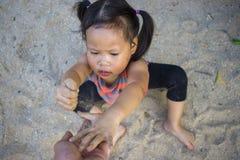 Det lyckliga barnet som spelar med sand, den roliga asiatiska familjen i, parkerar royaltyfria foton