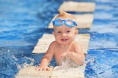 Det lyckliga barnet som spelar med vatten, plaskar i pöl Arkivfoton