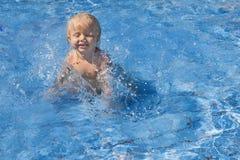 Det lyckliga barnet som spelar med vatten, plaskar i pöl Royaltyfri Fotografi
