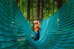 Det lyckliga barnet som tycker om i ett klättringaffärsföretag, parkerar Arkivfoto