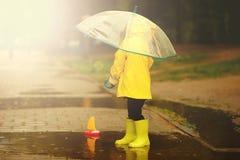 Det lyckliga barnet spelar i en pöl på en regnig dag för sommar en pojke i en gul regnrock går i parkerar royaltyfri fotografi