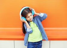 Det lyckliga barnet tycker om lyssnar till musik i hörlurar över den färgrika apelsinen arkivbilder