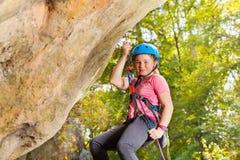 Det lyckliga barnet vaggar klättraren i hjälmen som abseiling Arkivbilder